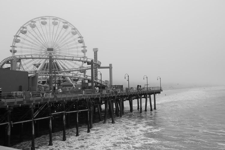Amusement Park On Pier Over Sea Against Sky During Foggy Weather
