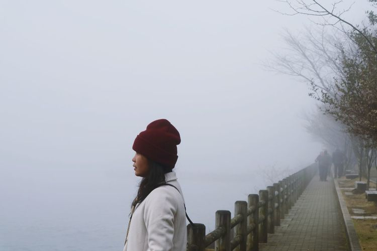Side view of woman standing by sea on footpath during foggy weather