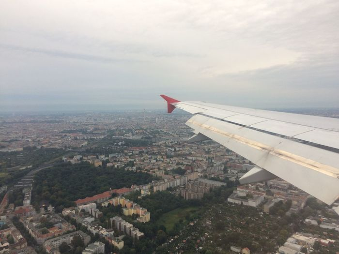Aerial view of airplane wing over cityscape