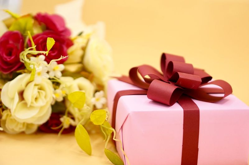Close-up of bouquet by christmas present on table