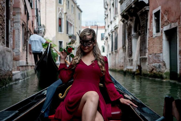 Portrait of smiling woman wearing mask while sitting on gondola in canal
