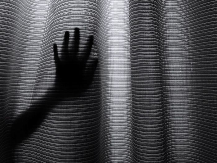 Silhouette Hand Touching Curtain