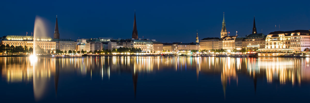 Illuminated City Scape of Hamburg seen across Alster River Building Exterior Reflection Architecture Built Structure City Water Illuminated Building Night Travel Destinations Waterfront Cityscape No People Government Blue Hamburg Town Hall Church Tower Fountain Alster Wide Angle