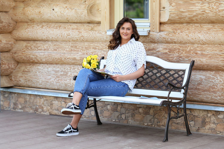 One Person Full Length Young Adult Sitting Real People Casual Clothing Lifestyles Young Women Women Seat Chair Leisure Activity Adult Portrait Front View Smiling Architecture Relaxation Holding Hairstyle Hair Fashion Beautiful Woman Outdoors Flower Girl