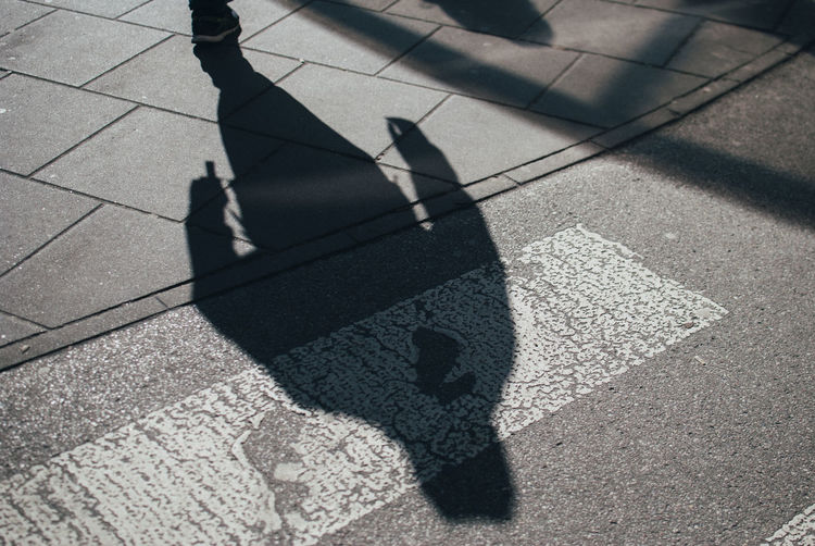 High angle view of person walking on street during sunny day