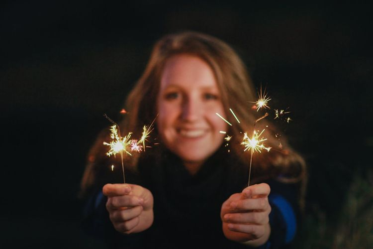 Close-Up Of Young Woman Holding Illuminated Sparklers At Night