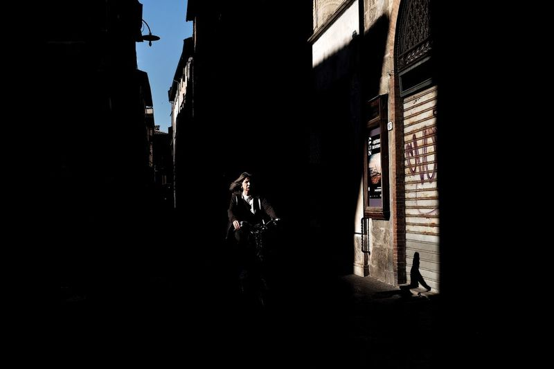 Silhouette of woman walking on building