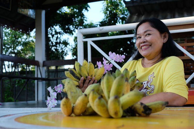 Portrait of smiling woman holding bananas while sitting at table
