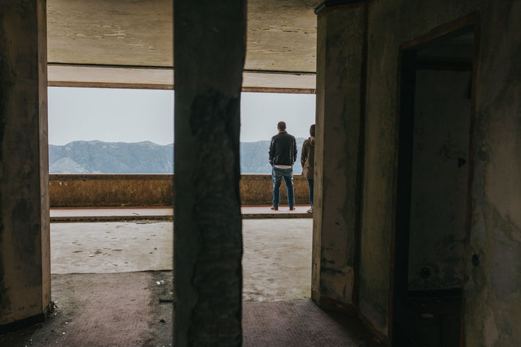 Rear View Of Man And Woman Standing At Abandoned Building