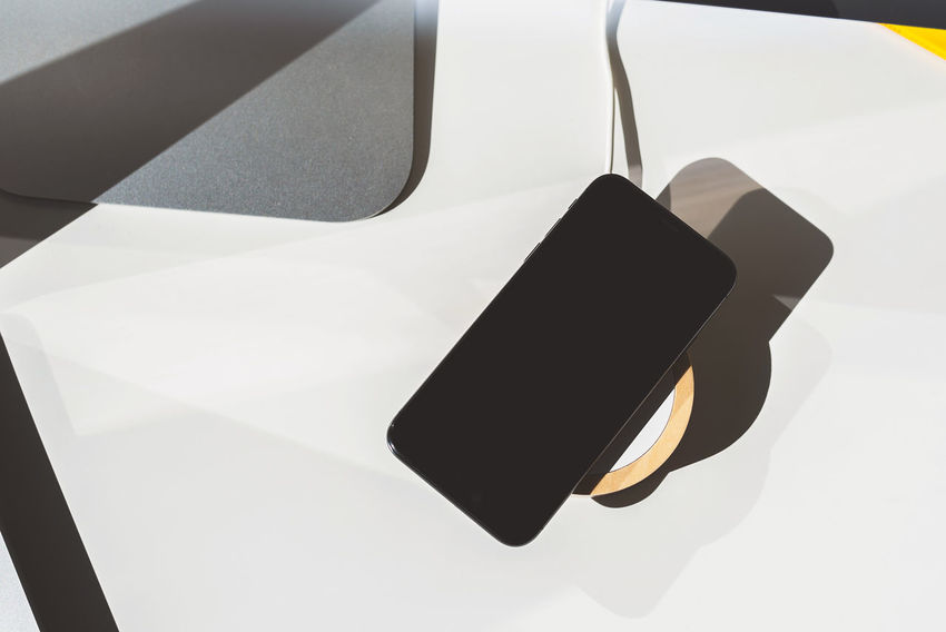 Mobile phone placed on wireless charger. Future technology concept Desk Mobile Phone Wireless Charging Wireless Charger Black Color Close-up Connection Day High Angle View Indoors  Mobile Phone No People Office Table Shadow Smart Phone Still Life Table Technology White Color Wireless Technology