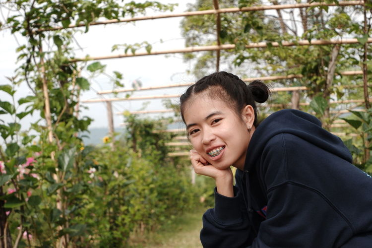 Portrait of a smiling young woman against plants