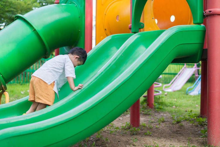 Boy playing on slide at playground