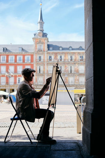 Man painting while sitting against buildings in city