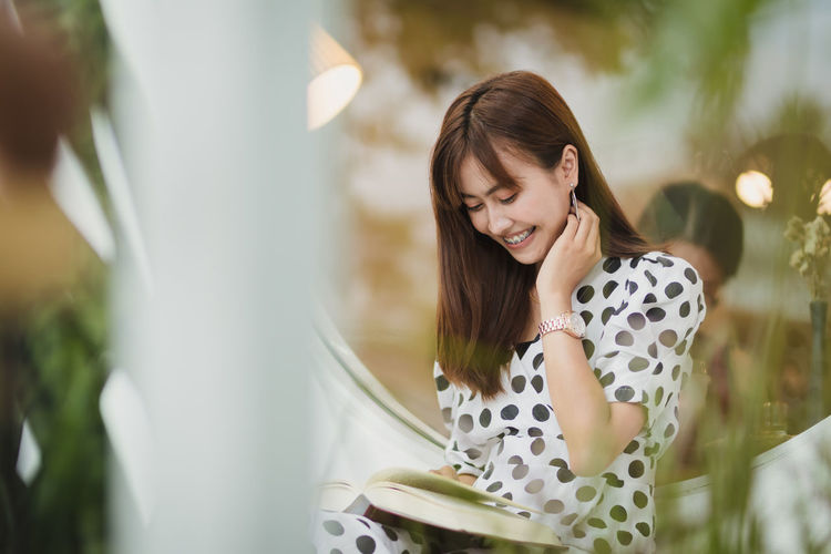 Smiling young woman reading book while sitting by window in cafe