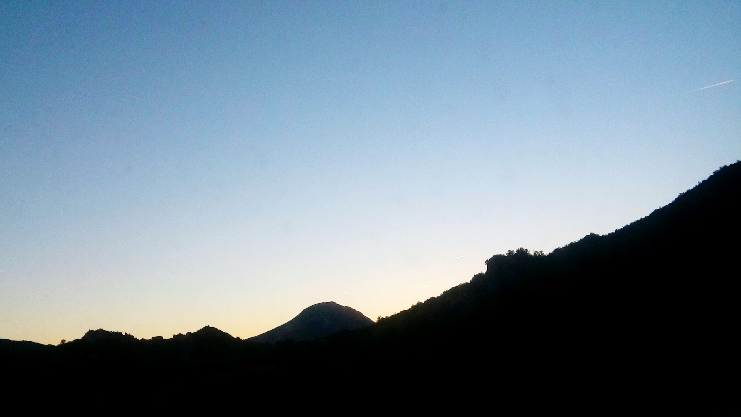mountain, silhouette, clear sky, tranquil scene, copy space, tranquility, scenics, beauty in nature, mountain range, nature, blue, non-urban scene, mountain peak, dark, outdoors, remote, no people, day, majestic, valley, physical geography, dawn, cliff, outline, wilderness area, geology, wilderness, solitude