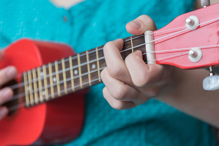 Girl playing chord on red soprano ukulele Fretboard Learning Music Red Acoustic Guitar Arts Chord Close-up Colorful Culture Education Female Fingers Girl Hand Music Education Musical Instrument Musician person Playing Song Soprano Ukulele String Instrument Student Ukulele