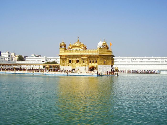 Golden temple by lake against sky
