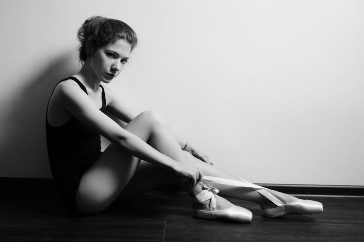 Young woman looking down while sitting on floor against wall