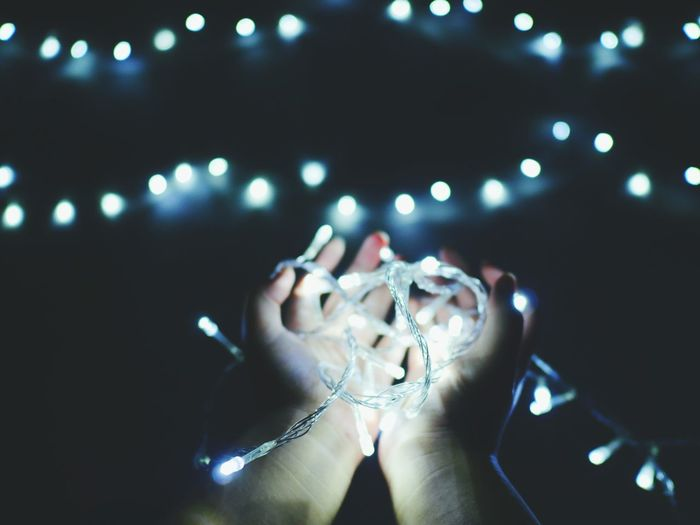 Close-up of hand holding illuminated string lights in darkroom