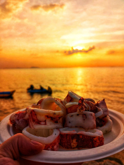 Meat in container on beach against sky during sunset