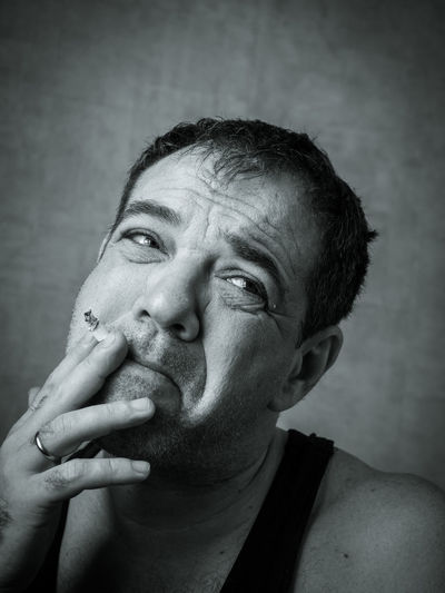 Close-up of man smoking cigarette against wall