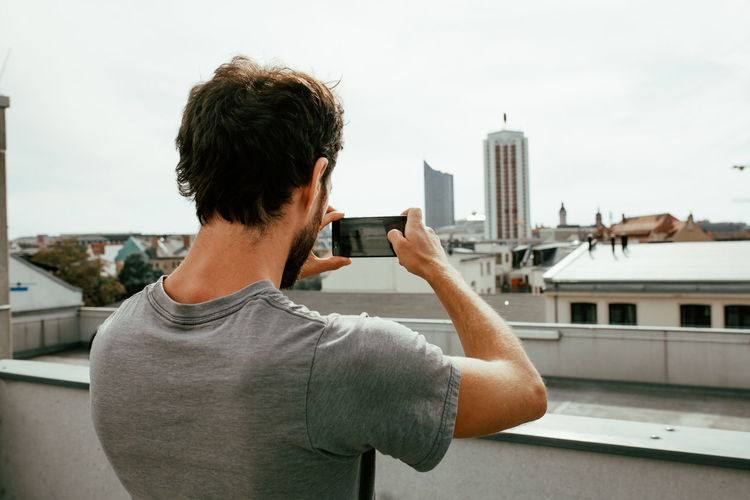 Rear view of man photographing city through mobile phone