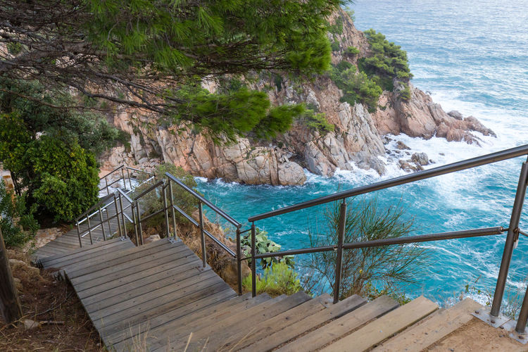 Wooden trail along the rocky coastline of Tossa de Mar, Spain Water Railing Sea Beauty In Nature Staircase Scenics - Nature Nature Tranquility Day No People Tranquil Scene Tree Rock Steps And Staircases Wood - Material High Angle View Rock - Object Outdoors SPAIN Tossa De Mar Path Trail Coastline