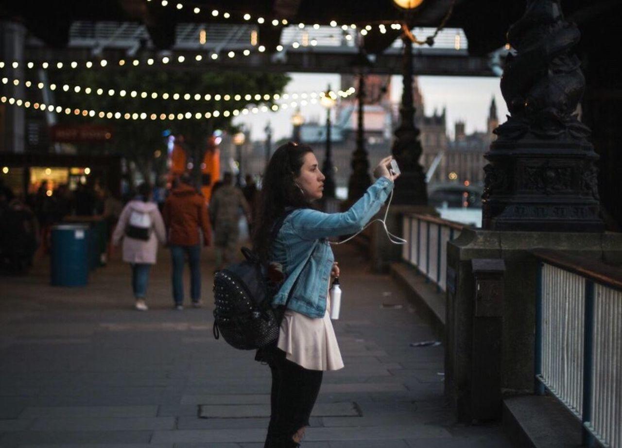 REAR VIEW OF WOMAN WALKING AT ILLUMINATED CITY