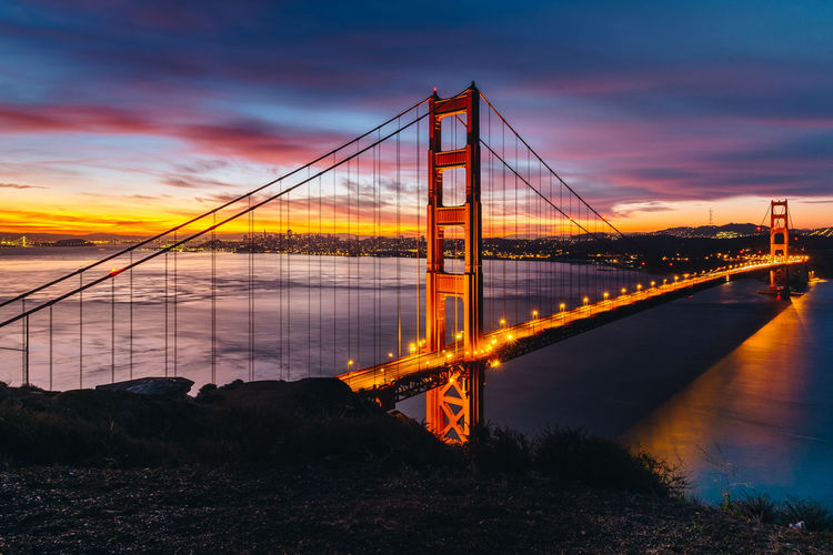 Golden gate bridge over river against sky during sunset