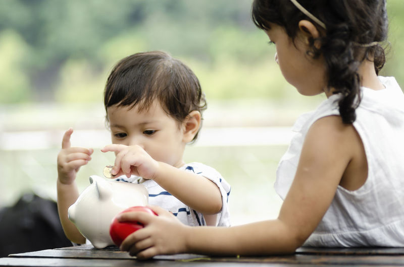 Learning financial and planning savings concept, young kids putting coins into piggy bank Child Childhood Two People Real People Males  Men Focus On Foreground Togetherness Boys Women Bonding Females Lifestyles Headshot Mother Family Sitting Looking Table People Innocence Son