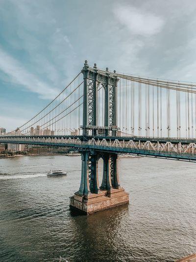 Suspension bridge over river against cloudy sky