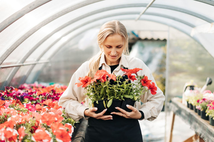 A young woman holds pots of flowers in a greenhouse. small business, garden center, flower shop