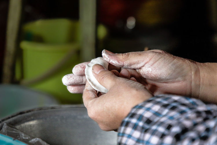 Close-up of man preparing chinese dumpling