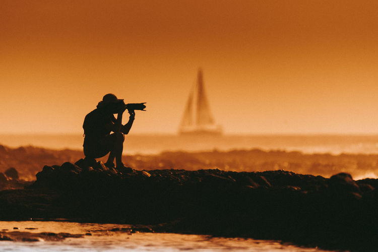 Silhouette man photographing at beach against clear sky during sunset
