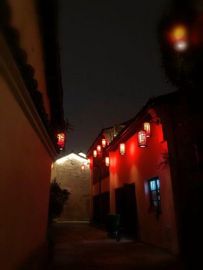Illuminated street amidst buildings against sky at night