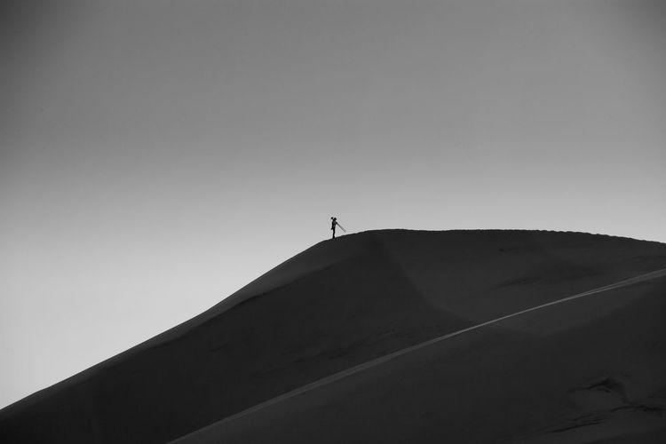Low angle view of silhouette person standing on sand dune against clear sky