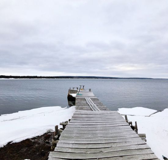 Wooden pier over lake against sky