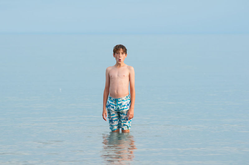 Full length of boy standing in sea