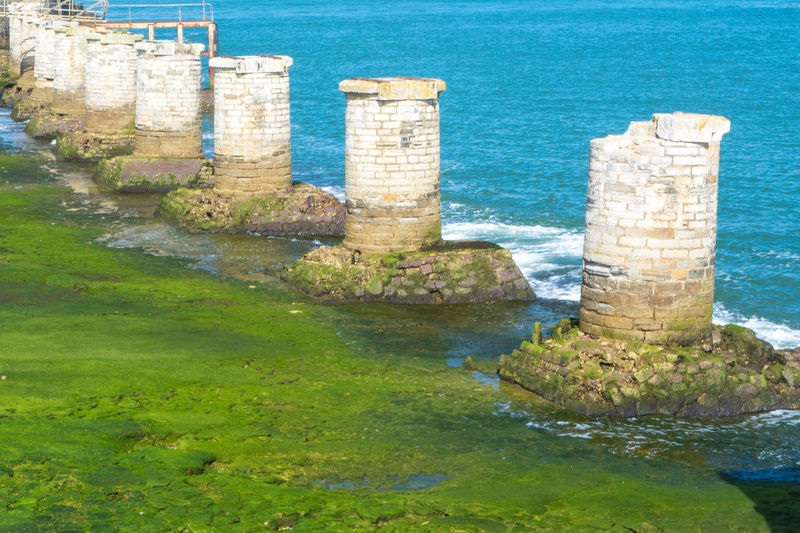 Anglet France - the old pier Anglet France Architecture Beauty In Nature Blue Built Structure Day Green Color Idyllic Moss Nature No People Ocean Outdoors Rippled Rock - Object Rock Formation Scenics Sea Tranquil Scene Tranquility Travel Destinations Water Premium Collection