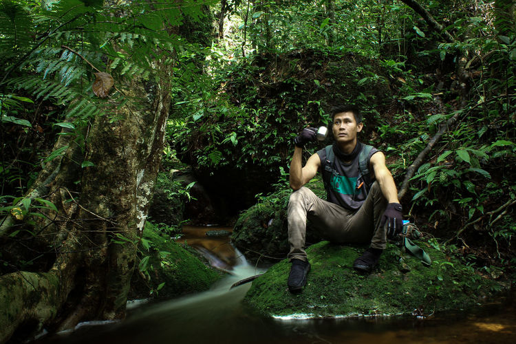 Adventurous male portrait exploring the forest while drinking in river