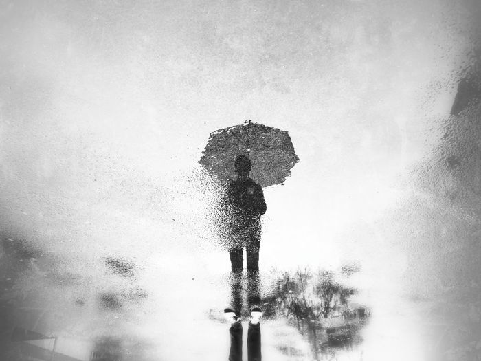 Silhouette of person holding umbrella