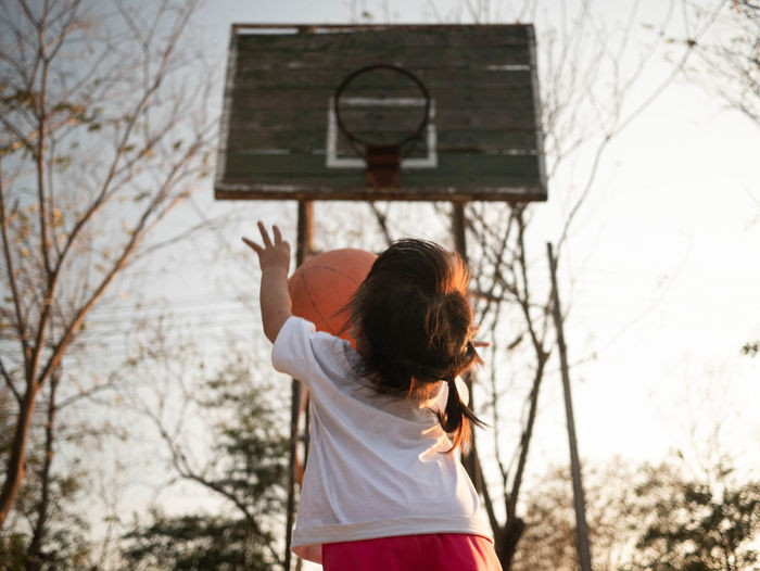 Rear view of girl playing basketball