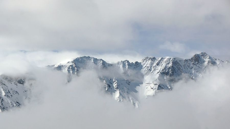 Scenic view of snowcapped mountains against cloudy sky at les arcs