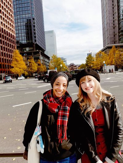 Portrait of smiling young women on street against buildings and sky in city