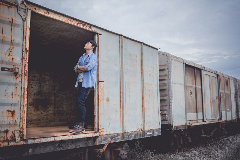 Sad young man standing in abandoned freight train against sky