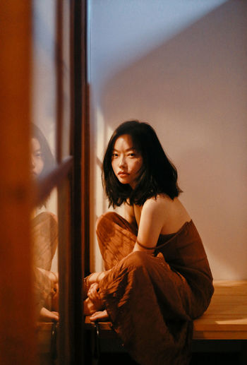 Young woman looking away while standing against window at home