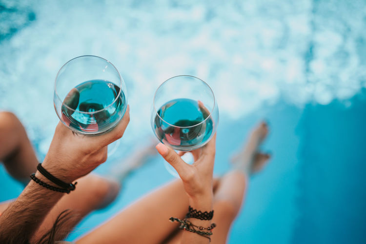 Close-up of hands holding glass in swimming pool
