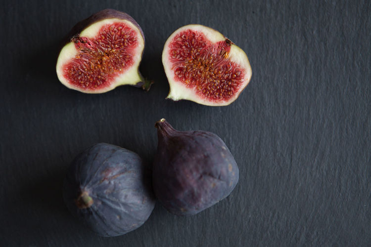 Beautiful fresh blue violet figs on dark stone background with empty copyspace close up vie from above. Healthy Eating Wellbeing Food And Drink Fruit Food Freshness Fig Cross Section Still Life Indoors  No People Close-up Group Of Objects Studio Shot High Angle View SLICE Table Directly Above Three Objects Gray Black Background Ripe Purple