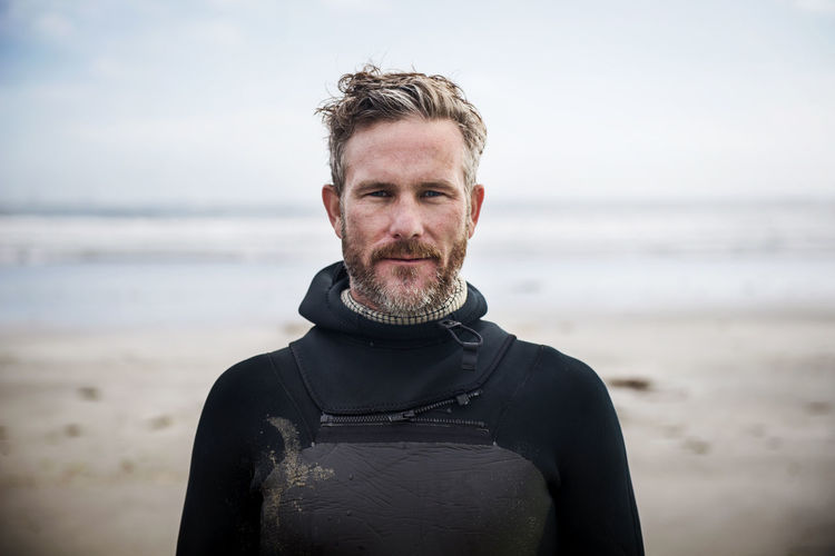 Portrait of confident surfer standing at beach