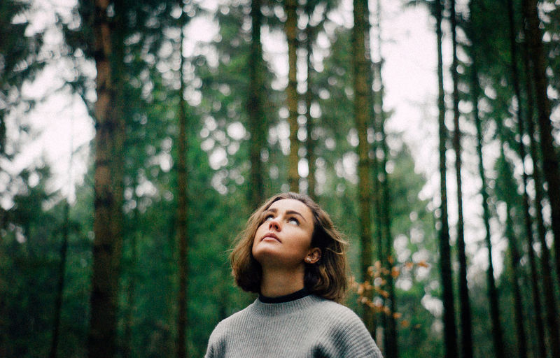 Young woman looking up while standing in forest